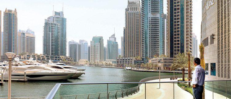 Adel_Sheni_enjoys_the_view_from_his_Dubai_Marina_apartment_tower